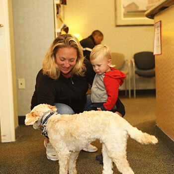 A mother and child petting Brady, our comfort dog