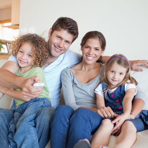 A family of four sitting on the couch while smiling and hugging