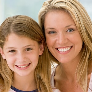 A girl with her mom smiling from the front on a light gray background