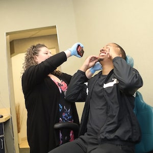 An assistant taking photos of a patient before they receive adult orthodontics