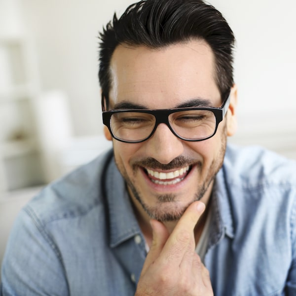 Man with dark hair and glasses looking down laughing after receiving orthodontic services