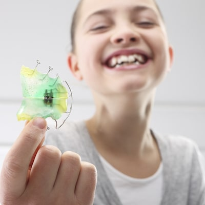 A little girl smiling and holding a retainer out in front of her