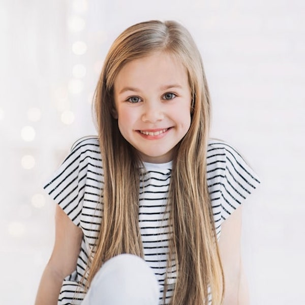 Young girl with long hair wearing a striped black and white top
