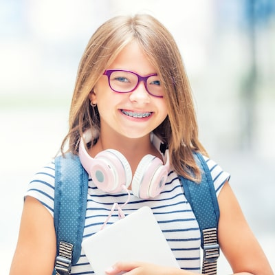 A little girl with purple glasses smiling after her children's orthodontics check-up