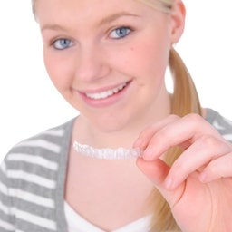 Young blonde girl smiling and holding a set of Invisalign clear aligners