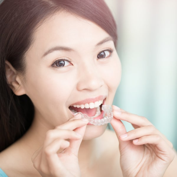 Woman with long dark hair putting in her Invisalign trays, which is one of our services