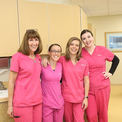 All our team of women smiling standing in the dental office wearing their pink uniforms