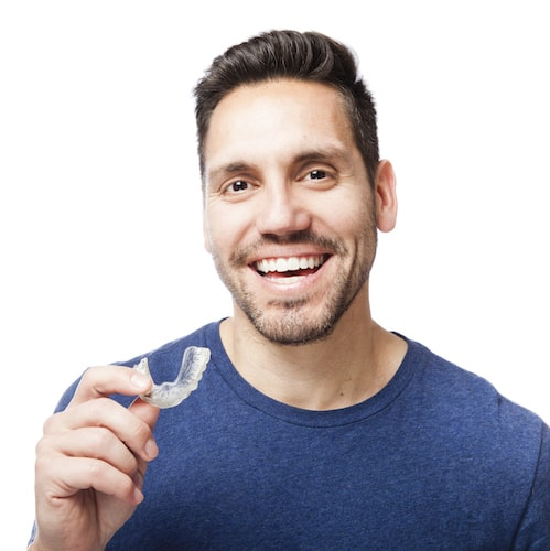 Young man holding an Invisalign® clear aligner and smiling
