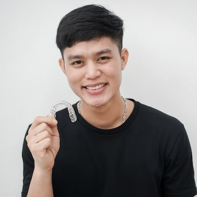 Young guy smiling and holding a set of Invisalign clear aligners